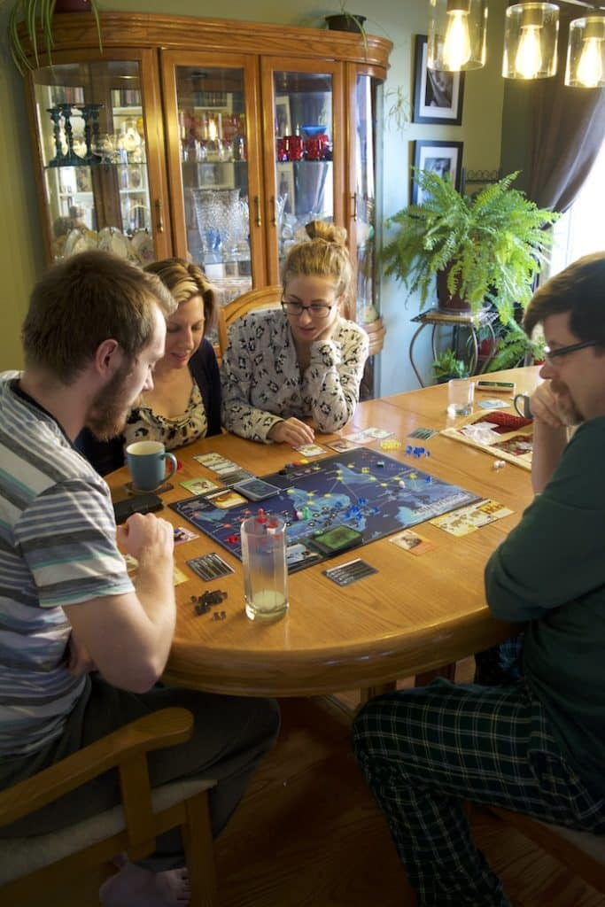 Family Playing Pandemic 683x1024 - 20 Awesome Family Board Games To Play Together